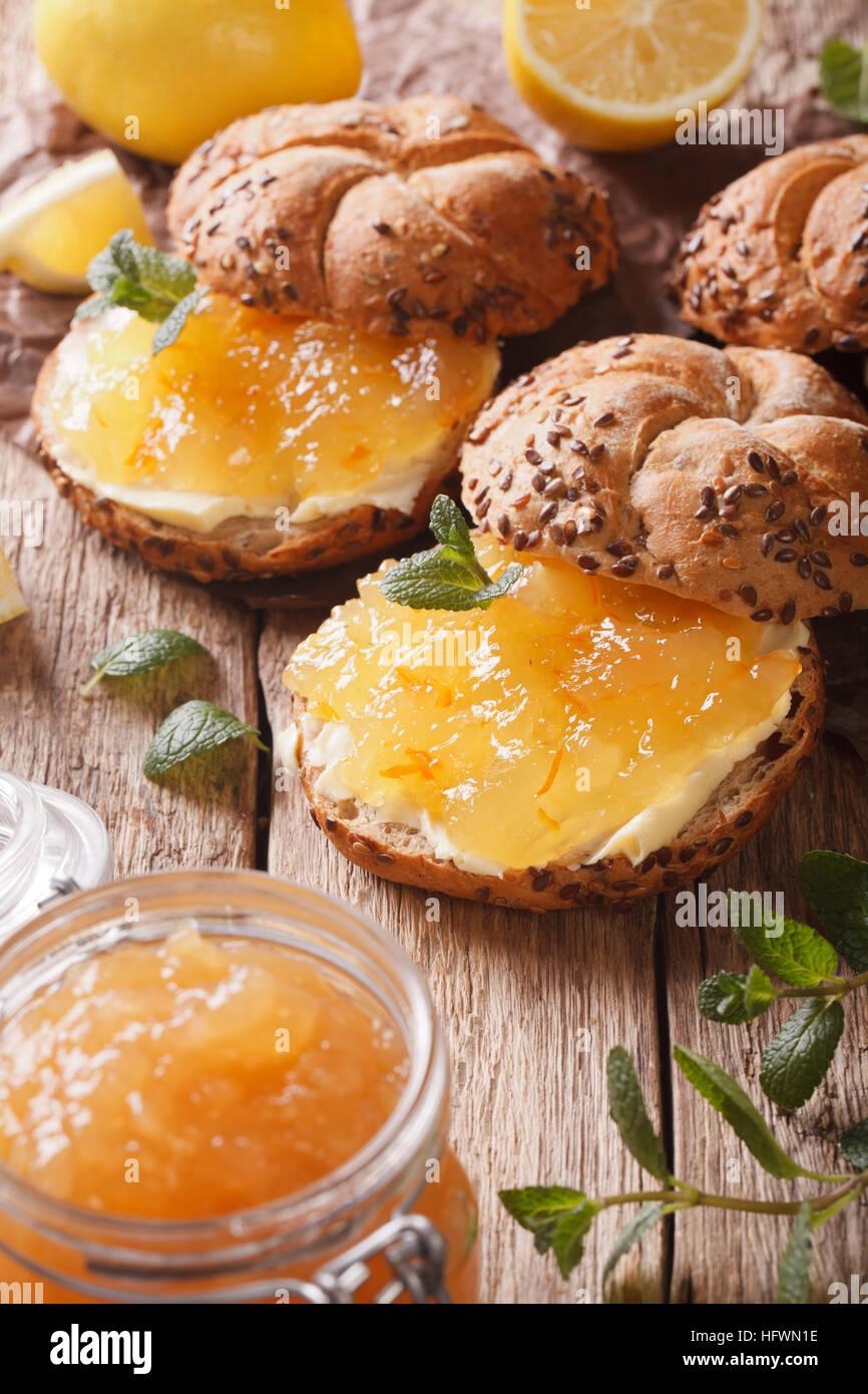 Bollos con mermelada de limón y mantequilla en la mesa macro vertical. Imagen De Stock