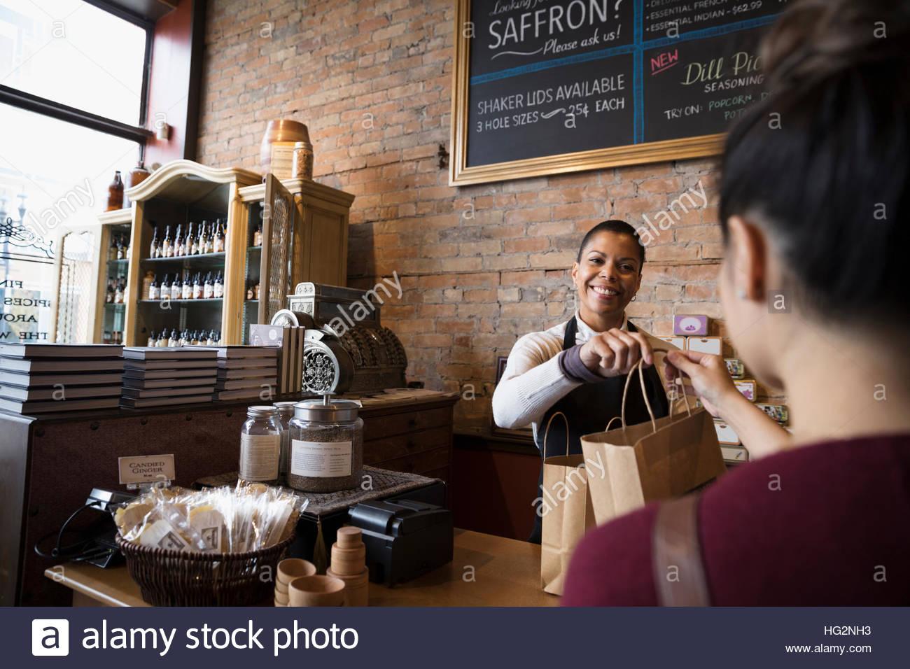 Mujer sonriente dueño de la tienda de especias dando bolsas de compras al cliente en el mostrador Foto de stock