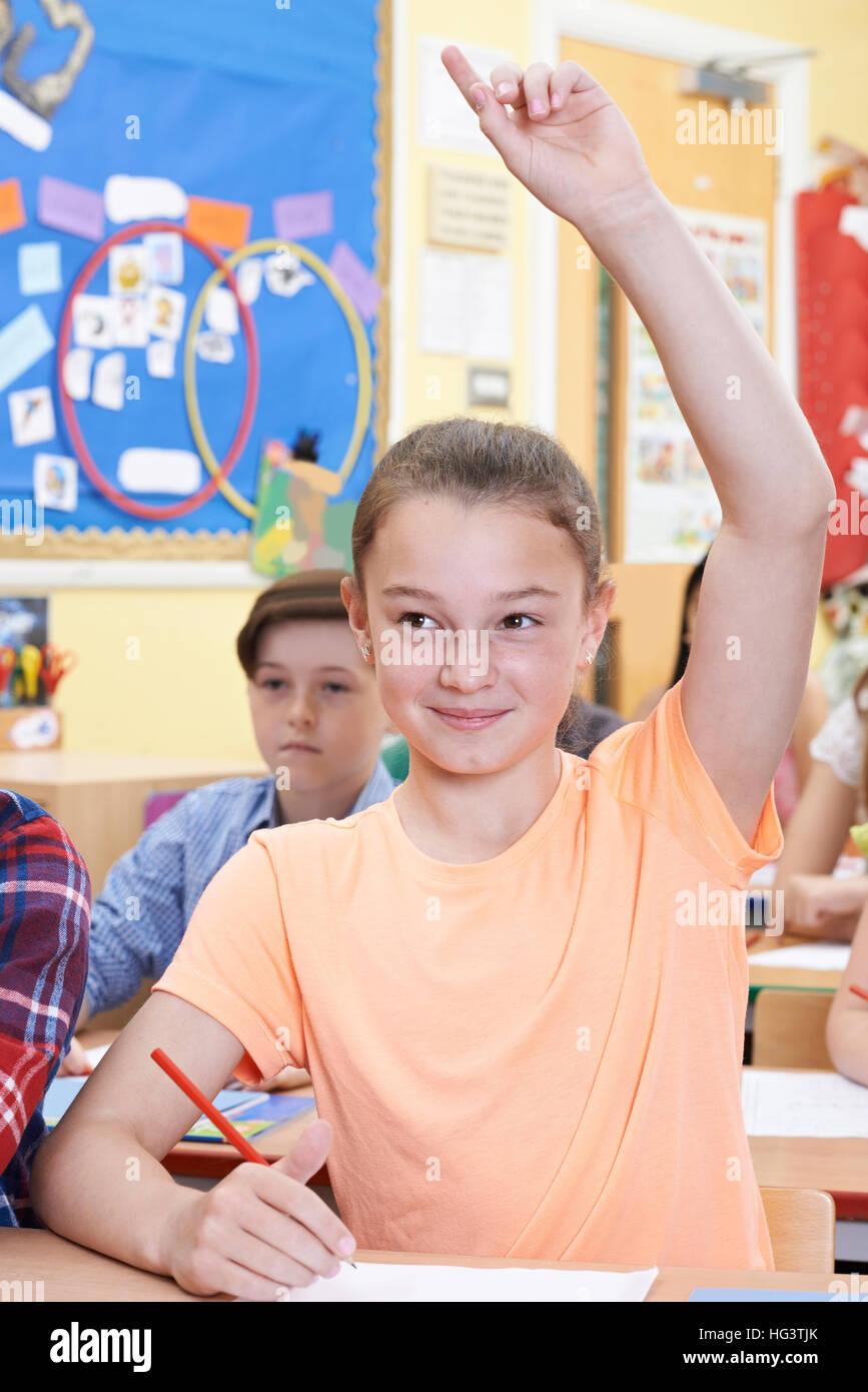 Estudiante levantando la mano para responder a la pregunta sobre la clase Imagen De Stock