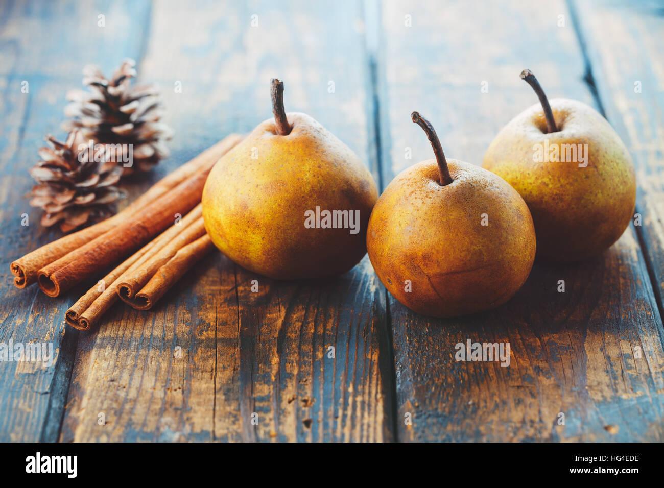 Peras orgánicos con palitos de canela en una mesa de madera Imagen De Stock