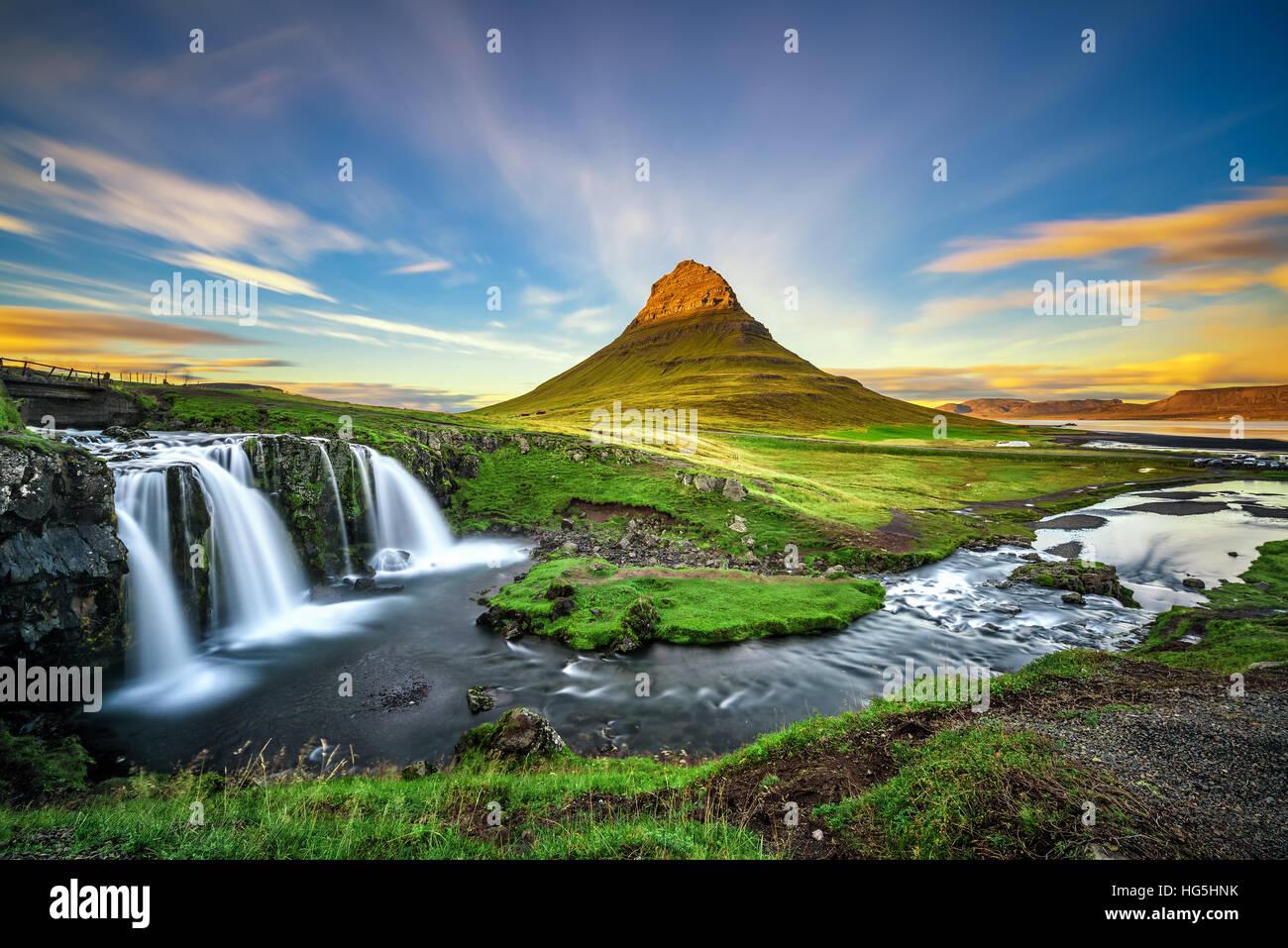 Verano atardecer en la famosa montaña Kirkjufell Kirkjufellsfoss cascada con en el fondo en Islandia. Imagen De Stock