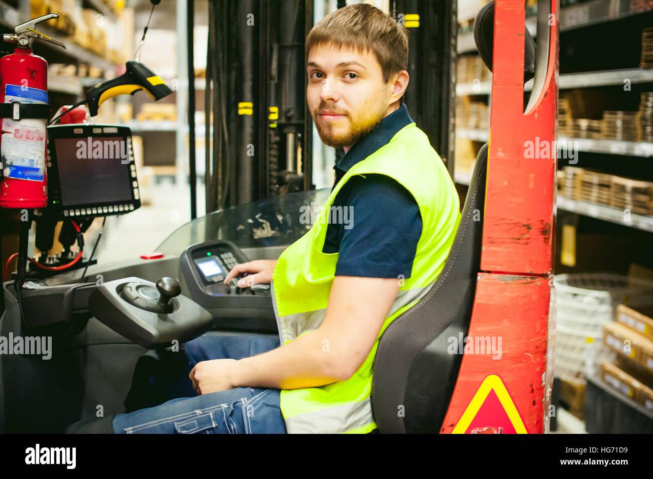 El hombre conductor Reachtruck ocupado trabajando almacén logístico store Imagen De Stock