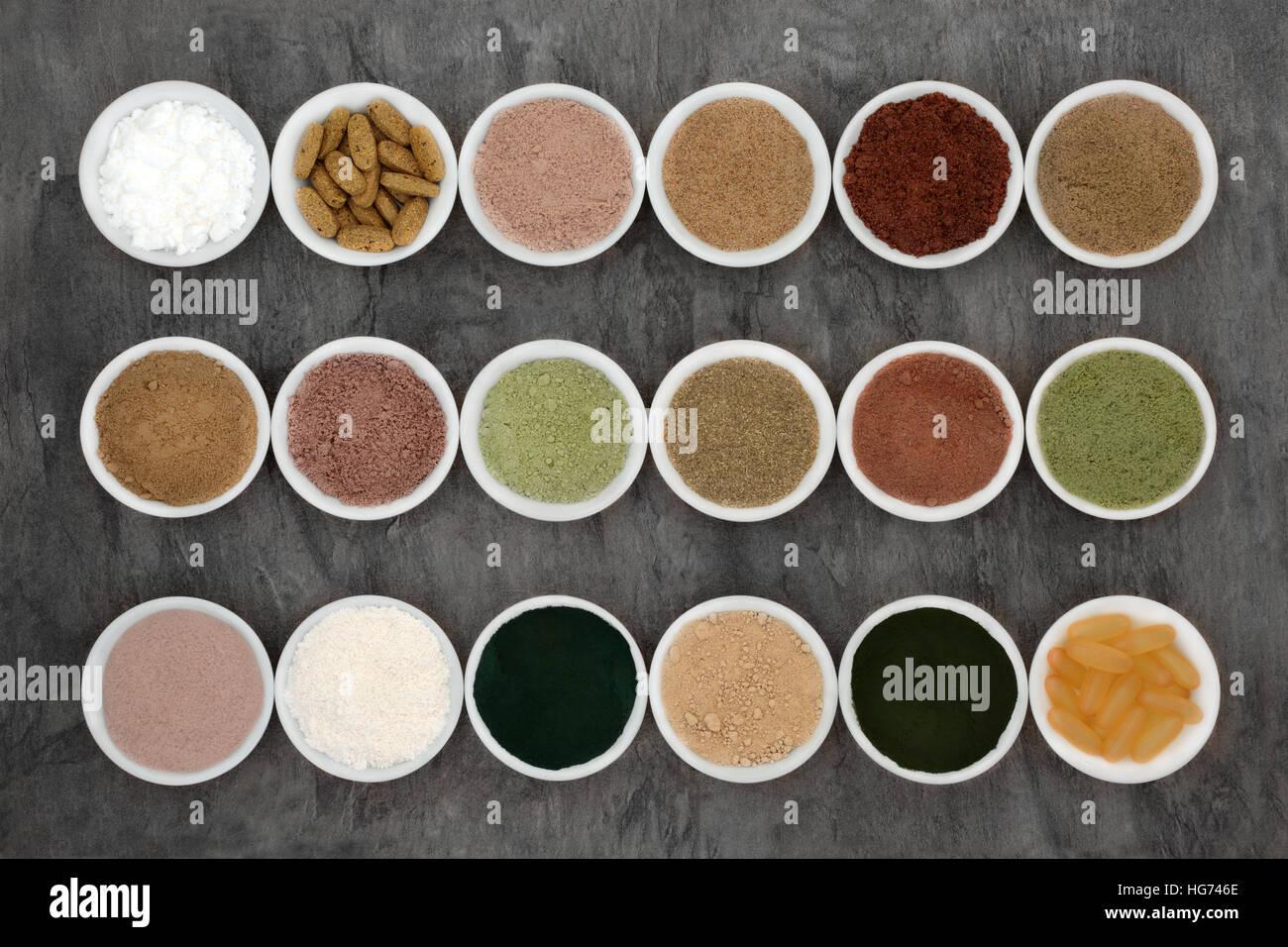 Polvos body building y suplementos en cuencos de porcelana sobre fondo de mármol. Imagen De Stock