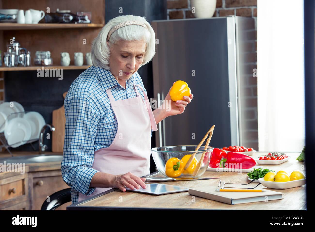 Mujer mayor utilizando digital tablet en la cocina mientras prepara ensalada de verduras Imagen De Stock