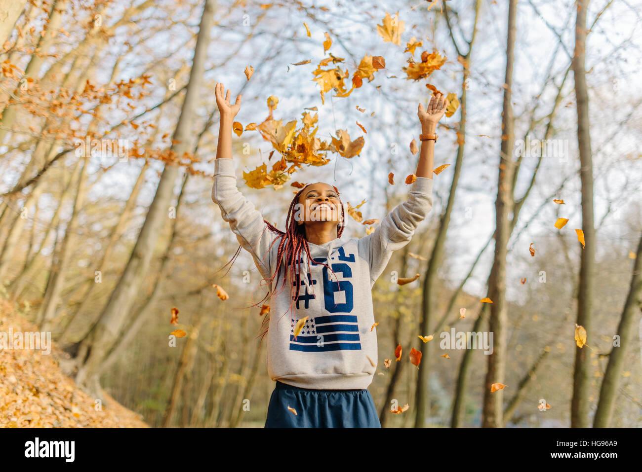 Muchacha africana jugando con manojo de hojas, disfrutando de otoño cálido día en el parque. Divertirse Imagen De Stock