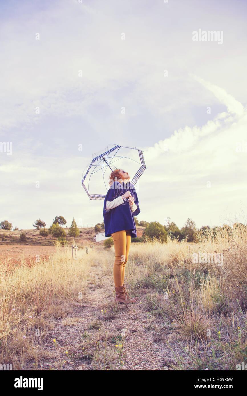 Mujer con un paraguas transparente y un soleado día de otoño Imagen De Stock