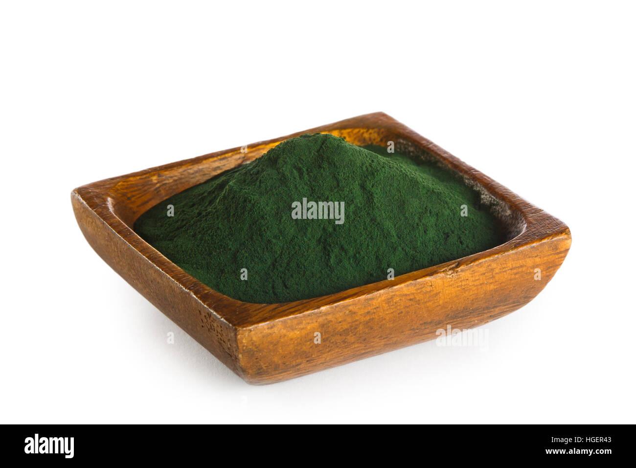 La Spirulina en polvo en el tazón de madera aislado sobre fondo blanco. Súper alimento Imagen De Stock