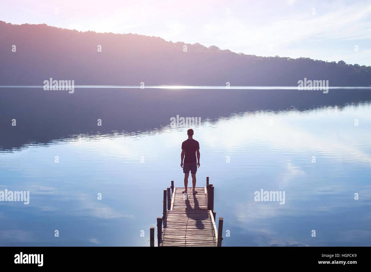 Soñador, silueta de hombre de pie en el muelle de madera del lago al atardecer, la fuerza humana, la psicología Imagen De Stock
