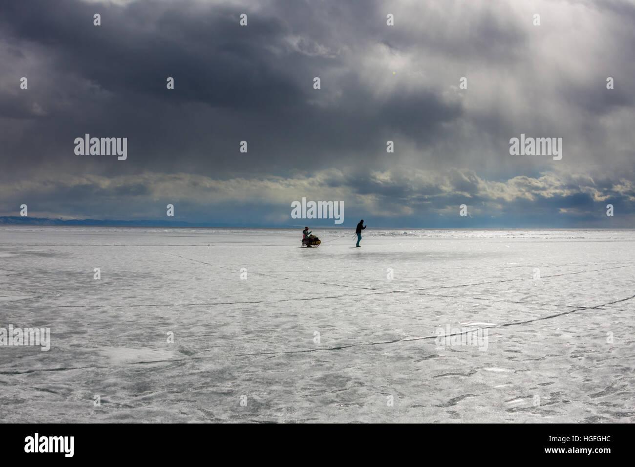 Una mujer y un hombre con un trineo y trekking pole es el hielo de Baikal Imagen De Stock
