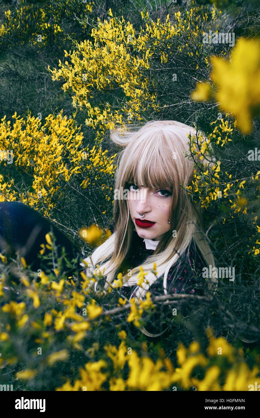 Retrato de una mujer joven entre un montón de flores amarillas Imagen De Stock
