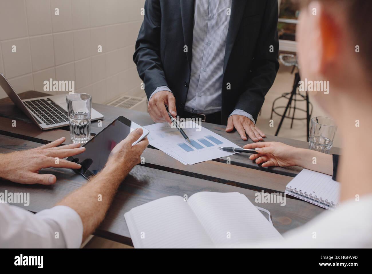Primer plano del equipo de profesionales que se reunión con la tableta digital y gráficos. Gente discutiendo Imagen De Stock