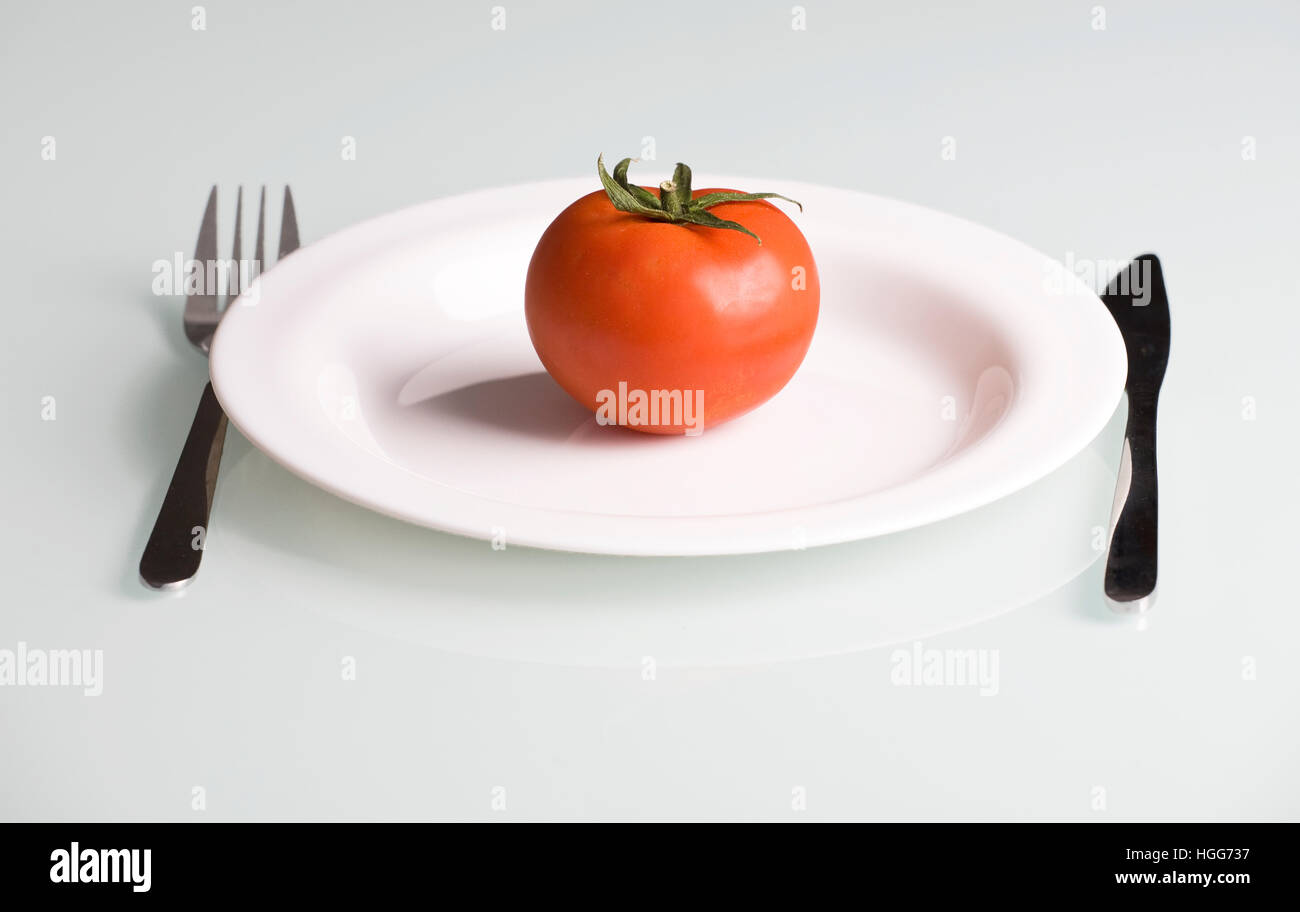 Tomate en un plato blanco con un tenedor y un cuchillo, en un cuadro blanco Imagen De Stock