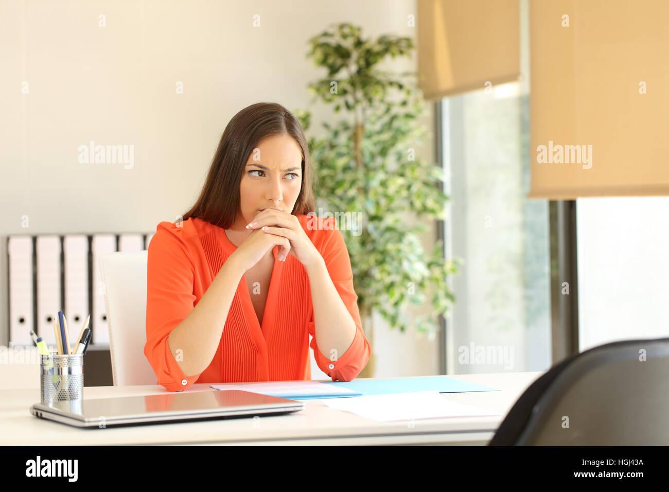 Pensativo y nervioso mujer esperando el entrevistador durante una entrevista de trabajo en un escritorio en la oficina Imagen De Stock