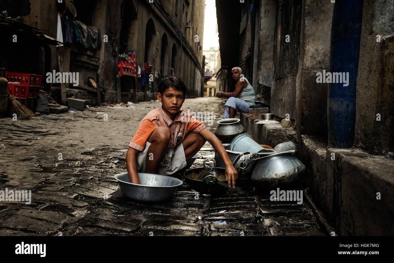Un muchacho lavando la ropa en el callejón de los tugurios de Calcuta. Imagen De Stock