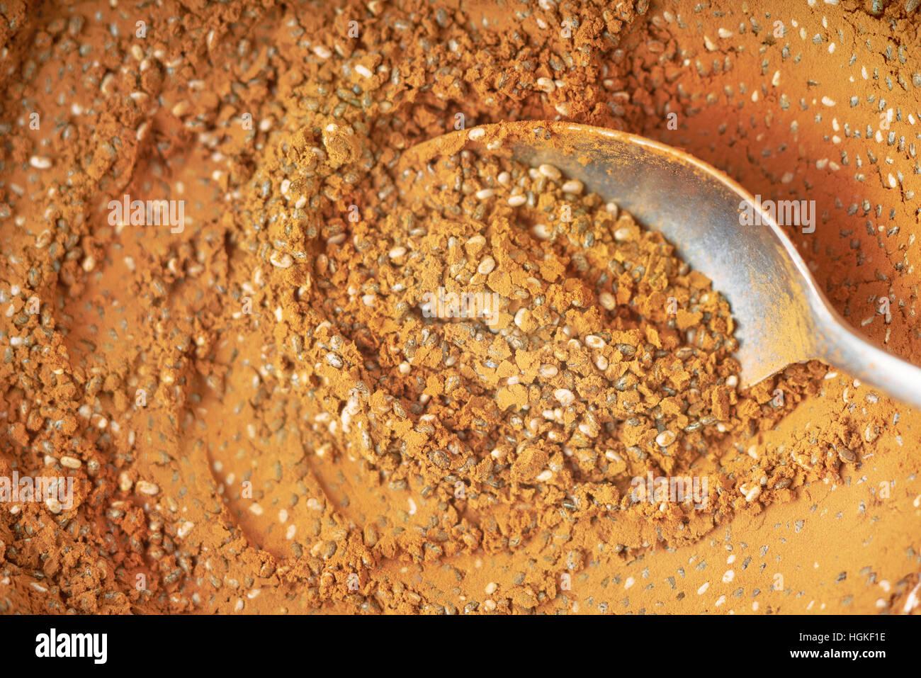 Cacao en polvo y semillas de chia mezclar con una cuchara de cerca de fondo Imagen De Stock