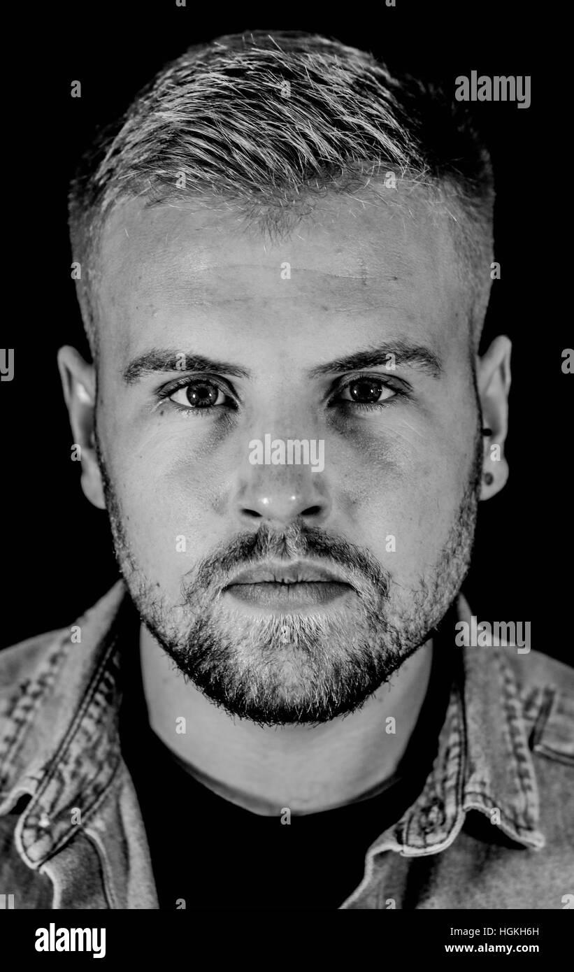 Retrato de un hombre barbado veinteañero mirando a la cámara Foto de stock