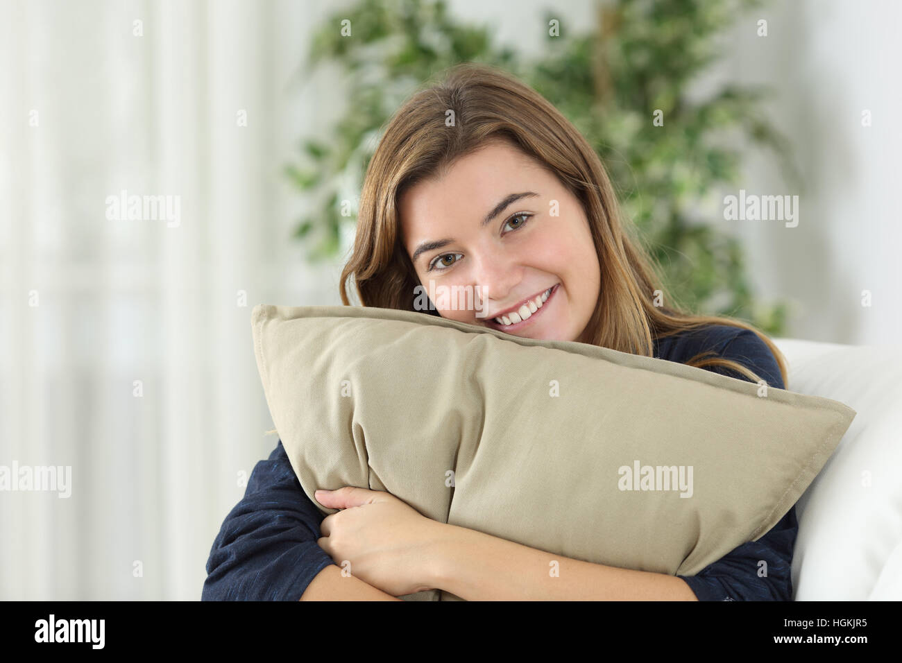Feliz jovencita posando mirando estás sentado en un sofá en el salón de casa Imagen De Stock