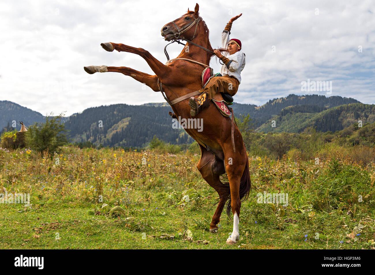 Jinete kazajo en trajes nacionales, obtiene su caballo criado en Almaty, Kazajstán. Imagen De Stock