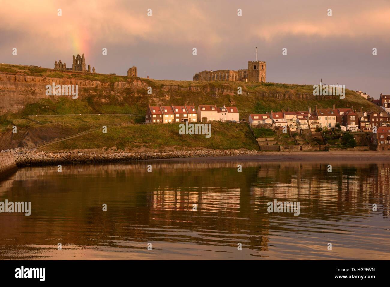 Vista del East Cliff (casas, la Iglesia de Santa María, ruinas de la abadía y rainbow) reflejada en el mar - Whitby, Foto de stock