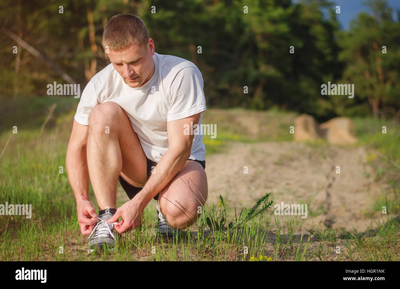 Atlético joven hombre atando los cordones de los zapatos