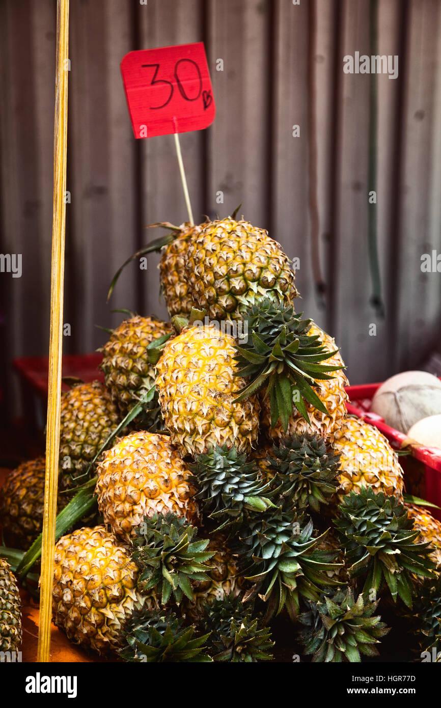 Montón de piña sin pelar con etiqueta de precio en el mercado mostrador. Muchos fruta amarilla apiladas Imagen De Stock