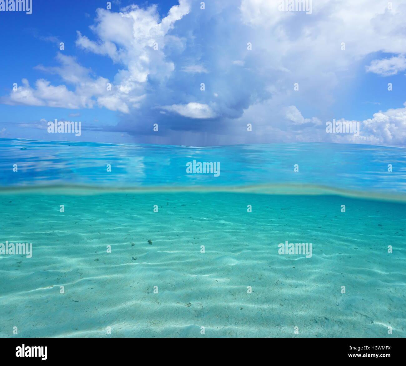 Mitad y mitad, Océano Pacífico seascape, fondos arenosos poco profundos subacuático con nublado cielo Imagen De Stock