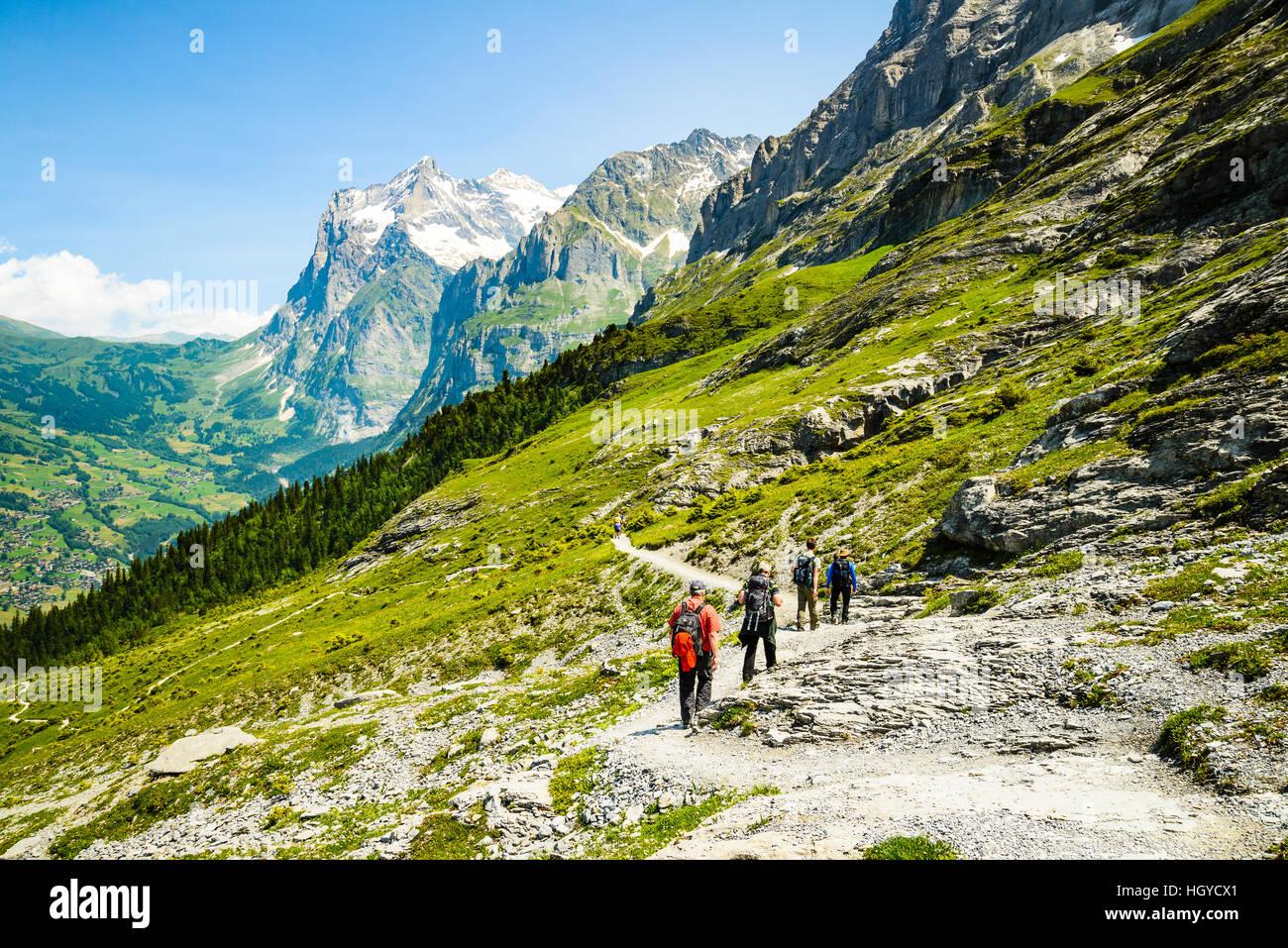 Los caminantes en el sendero del Eiger Grindelwald, Suiza con el valle y el pico Wetterhorn detrás Foto de stock