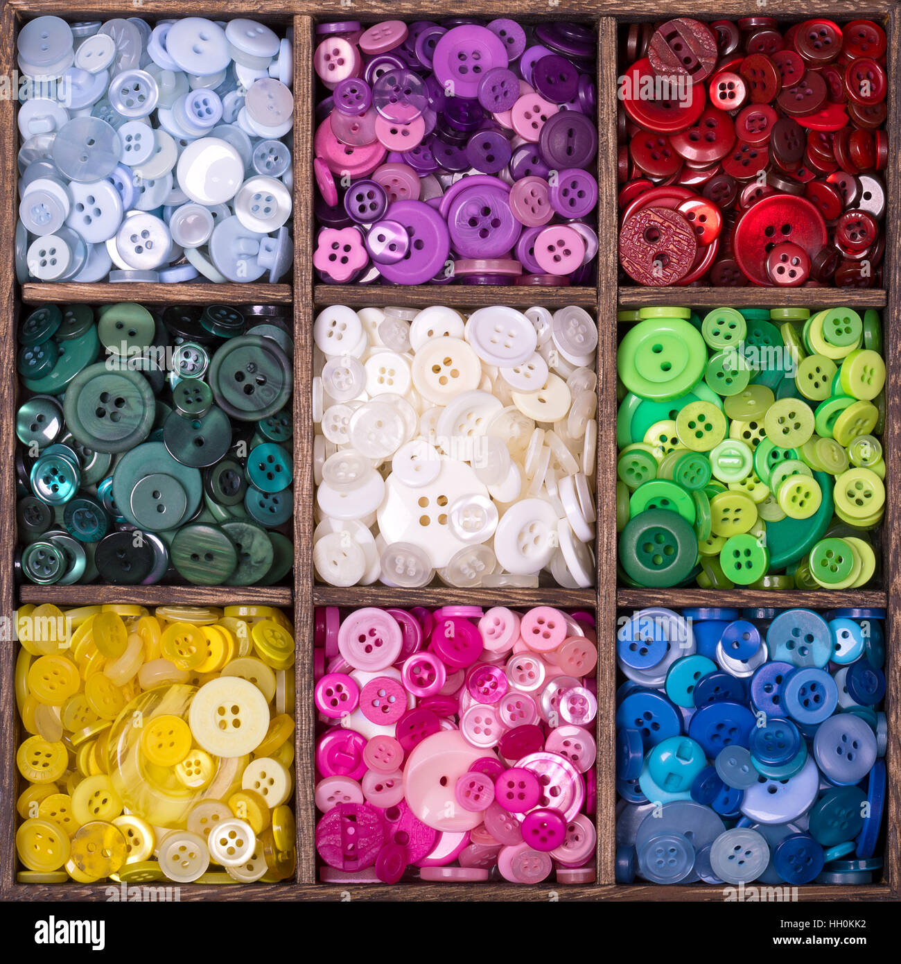 Caja de almacenamiento de madera cuadrada con 9 compartimentos, rellenos con una selección de coloridos botones agrupados por color. Foto de stock