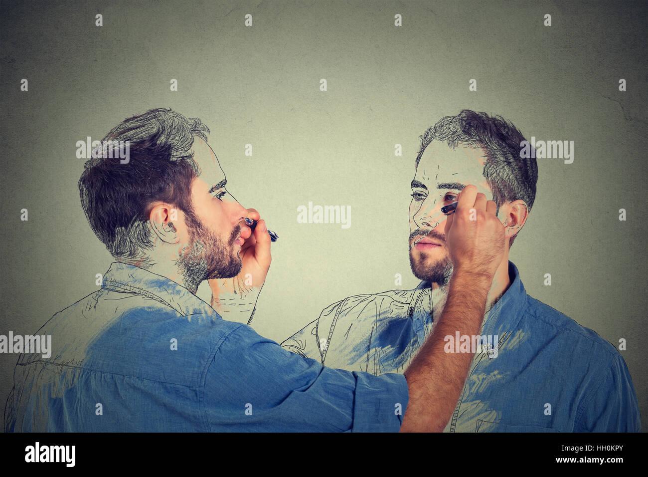 Crear usted mismo concepto. Guapo joven una imagen de dibujo, Boceto de sí mismo en la pared gris de fondo. Imagen De Stock