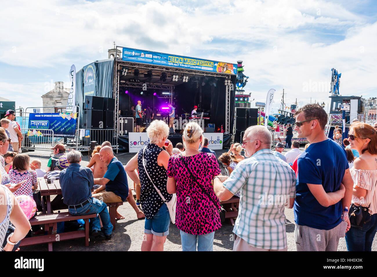 Inglaterra, Ramsgate. Paseo marítimo público viendo Kent, párrafo 1, de la banda tocando en escenario cubierto en la canícula estival. Vista desde detrás del público. Foto de stock