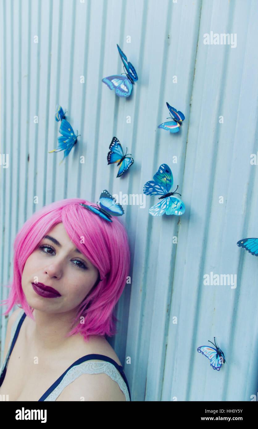 Soñador retrato de una mujer joven con el pelo rosa y un montón de mariposas azules volando a su alrededor. Imagen De Stock