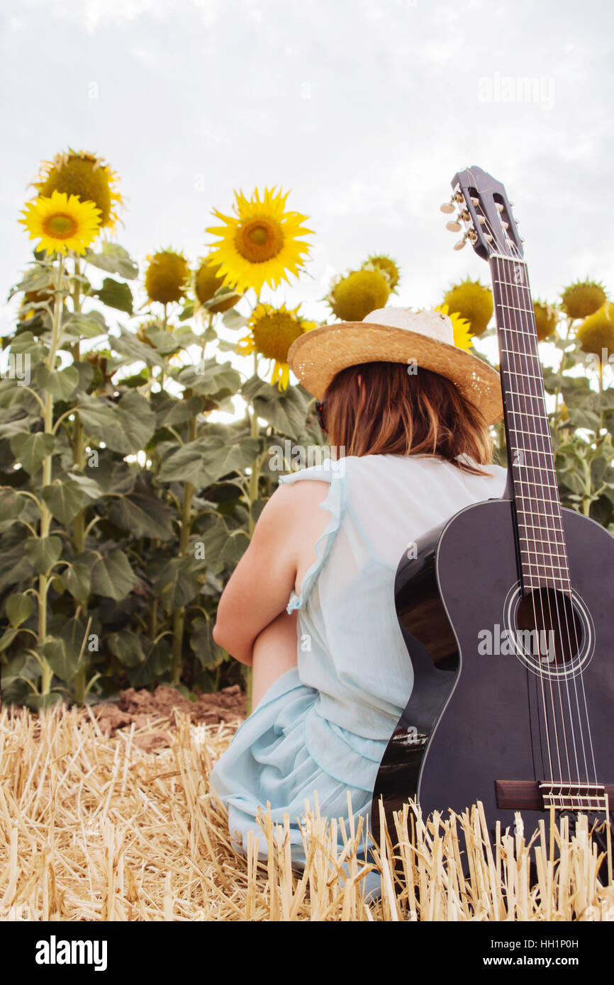 Mujer joven en verano con su guitarra negra delante de un montón de girasoles Imagen De Stock