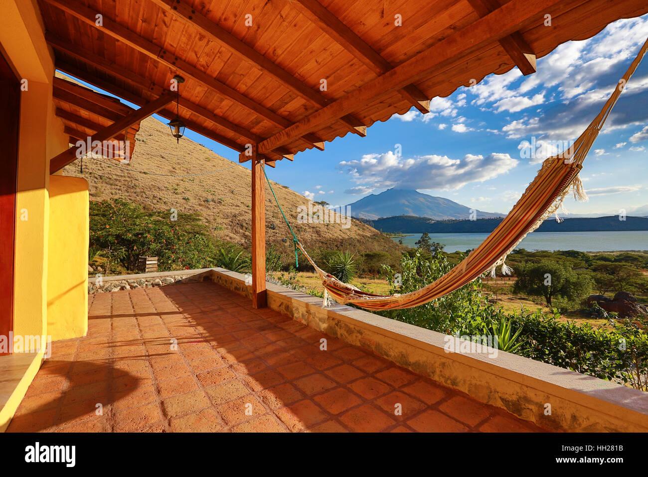 Hamaca en un patio con volcán en el fondo del lago Yahuarcocha cerca de Ibarra, Ecuador Imagen De Stock
