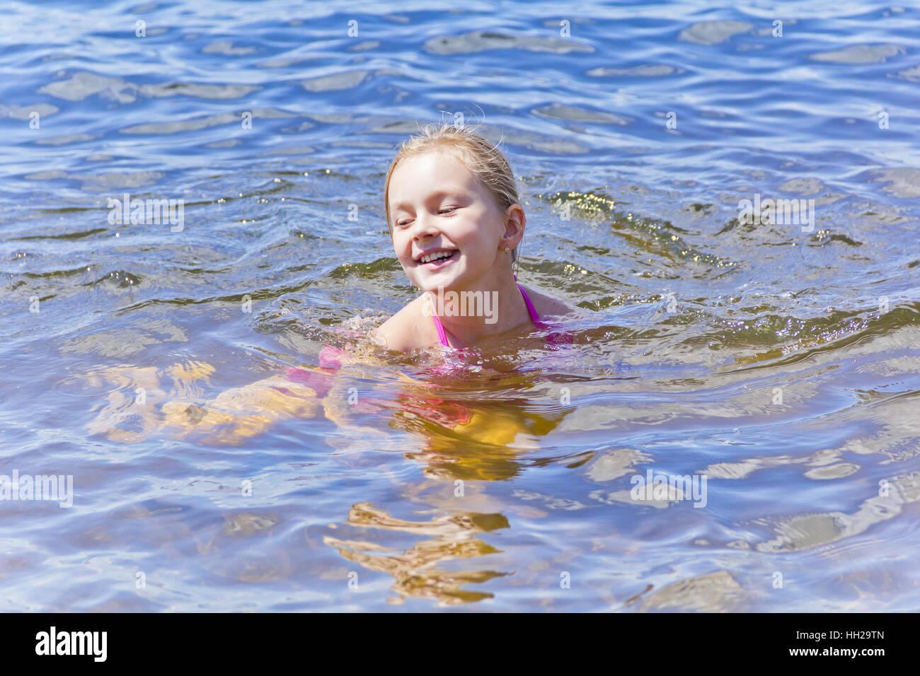 Natación cute sonriente niña de siete años de edad Imagen De Stock