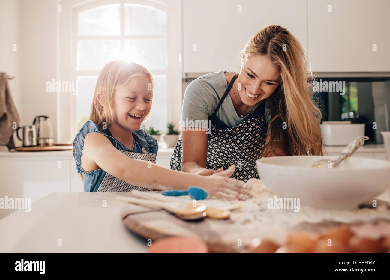 Niña feliz con su madre haciendo masa. Madre e hija en la cocina para hornear. Imagen De Stock