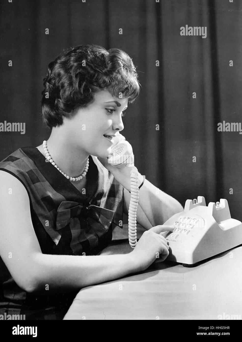 Un modelo experimental de un pulsador teléfono siendo desarrollado en los Laboratorios Bell Telephone es juzgado por Gayle Gerbe. El pulsador teléfono es factible hoy por los avances electrónicos que incluyen el transistor, inventado en los laboratorios Bell. Este pulsador particular diseño combina muchas características que promueven la máxima exactitud y que son preferidos por los usuarios. La disposición de botones es el resultado de meses de estudio de factores humanos. Foto de stock
