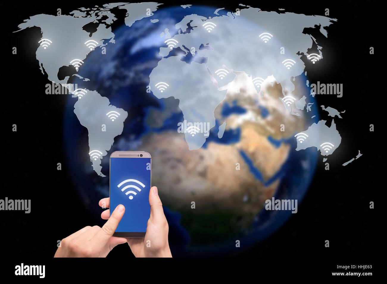 Mano sujetando el teléfono inteligente en el mapa mundial de la red de comunicación inalámbrica y Imagen De Stock