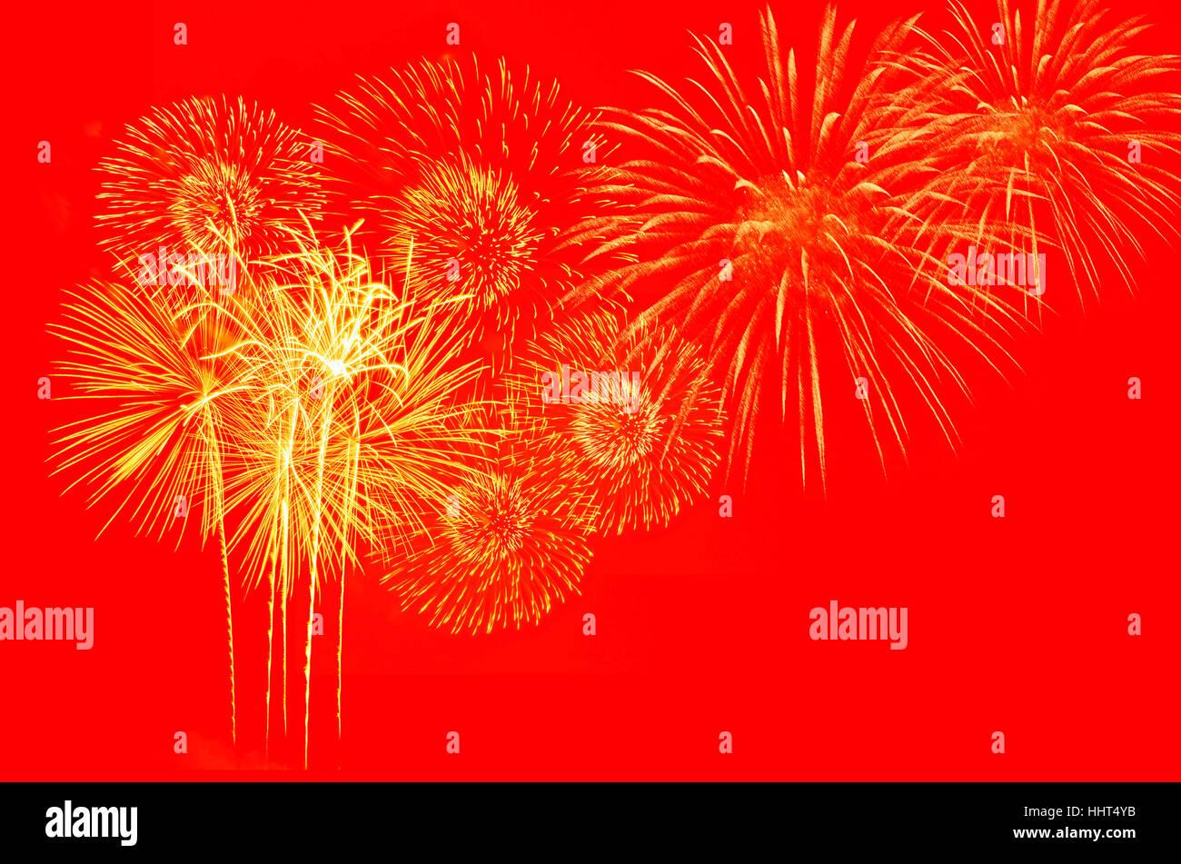 Fuegos artificiales de oro sobre fondo rojo. Foto de stock