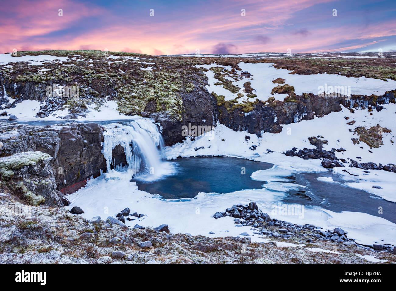 Una cascada fríos con nieve en las montañas de Islandia enmarcada por cielos pastel y el terreno escarpado ofrece Foto de stock