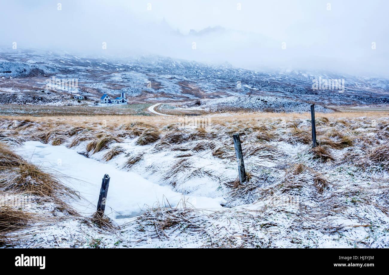 Un resfriado, una escena de nieve en Islandia muestra un río congelado y helado paisaje de pasto durante un día de invierno. Foto de stock