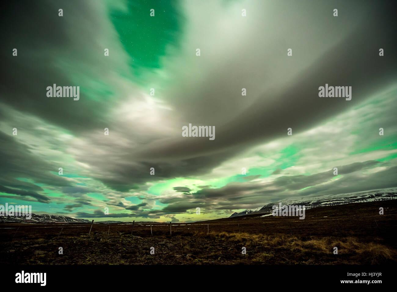 La Aurora Boreal brilla sobre un lago helado rodeado de baja nubosidad y estrellas Imagen De Stock