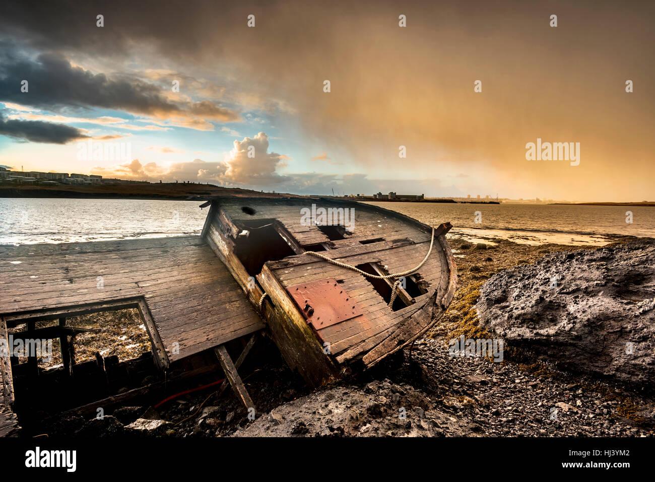 Un viejo barco de pesca abandonados desde el 1900 descansa sobre una playa remota como se pudre, exponiendo las Imagen De Stock