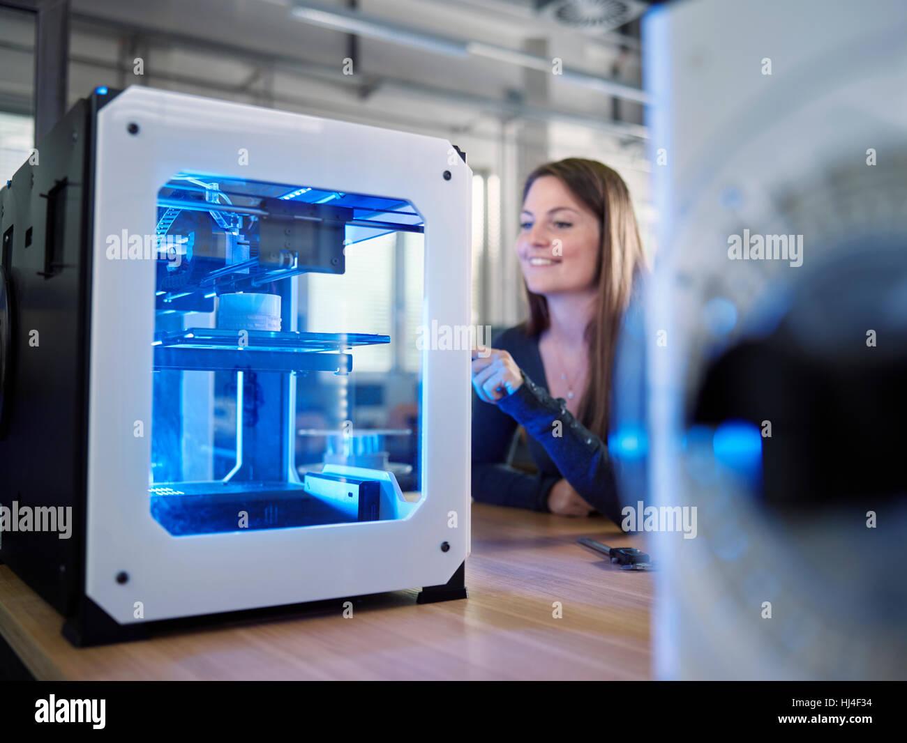 Empleado, 25-30 años, abriendo la impresora 3D en producción, laboratorio FabLab, Wattens, Tirol, Austria Imagen De Stock