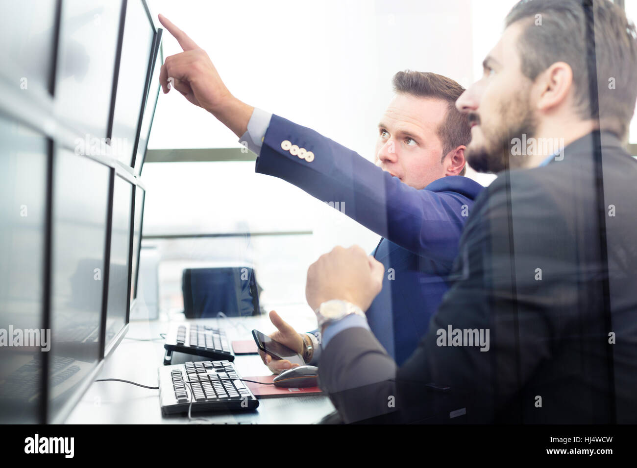 Stock Traders mirando pantallas de ordenador. Imagen De Stock