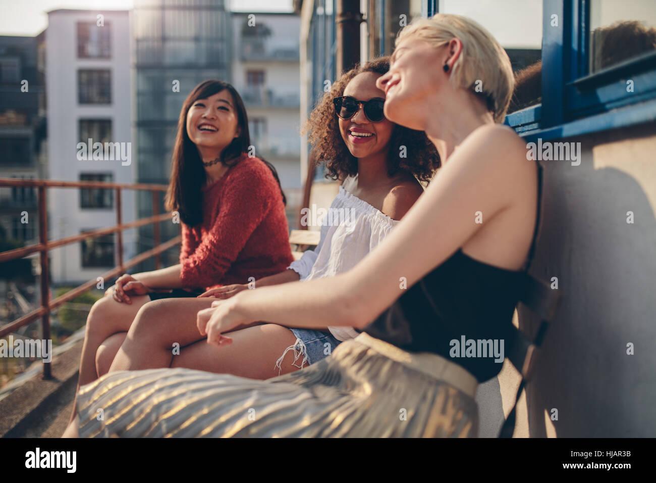 Tres amigas jóvenes sentados en el balcón y la diversión. Las mujeres relajarse al aire libre y conversando. Imagen De Stock