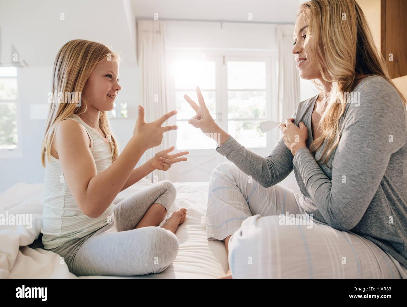 Vista lateral de disparo joven jugando con la niña en la cama, en su casa. Madre e hija jugar en el dormitorio. Imagen De Stock