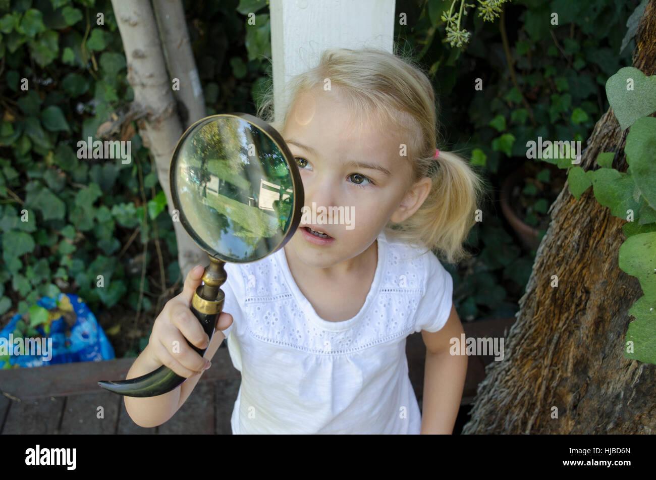 Joven mirando a través de una lupa Foto de stock