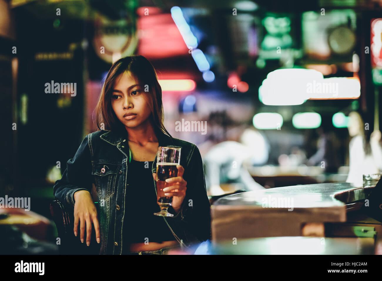 Vida nocturna, adulto chica esperando en el bar bebiendo bear Imagen De Stock