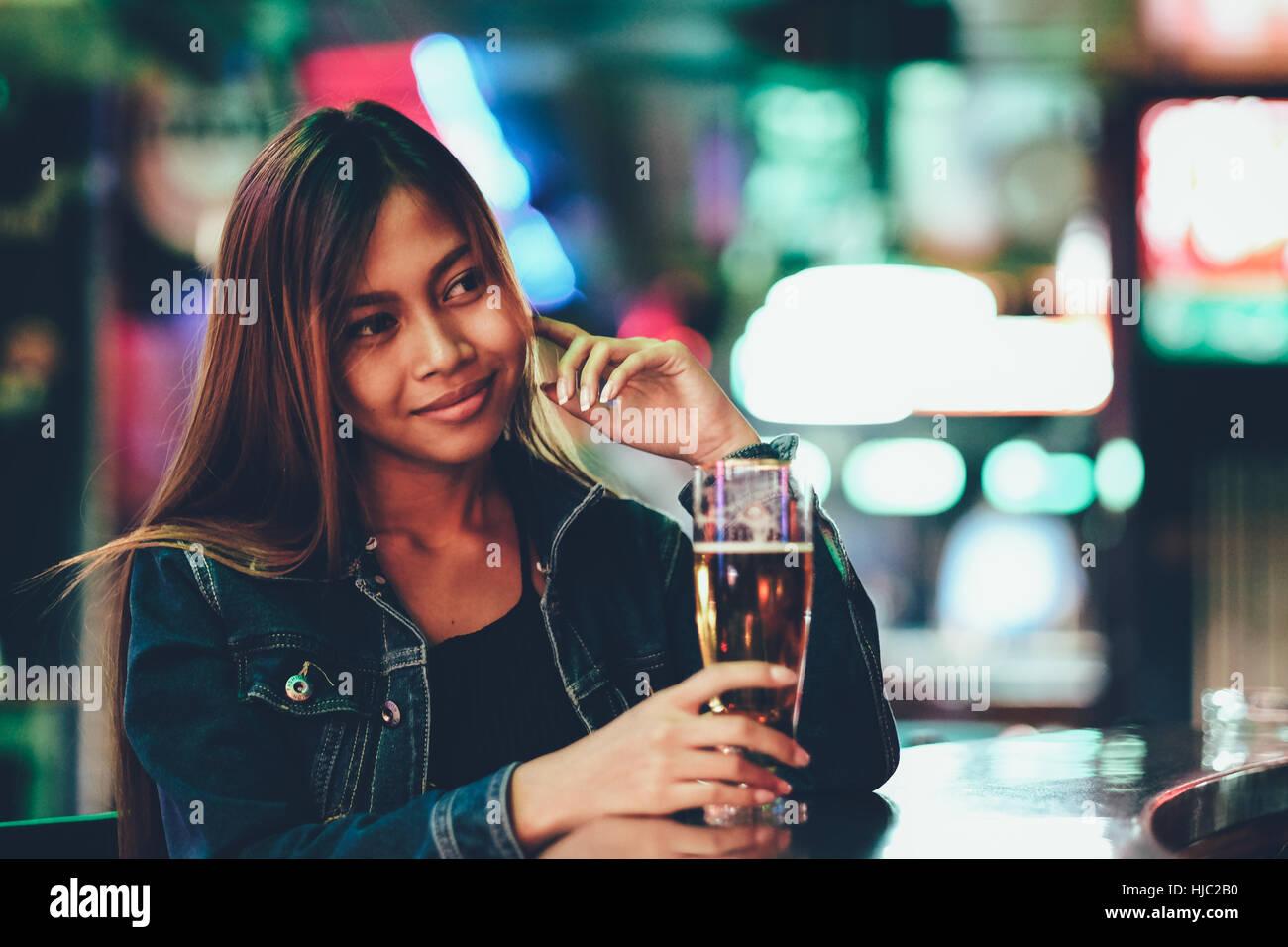 Vida nocturna, adulto chica esperando en el bar bebiendo bear Foto de stock