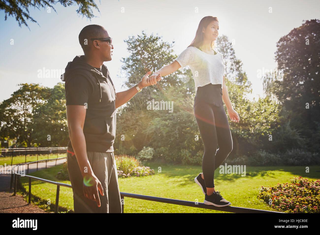 Mujer sosteniendo las manos con entrenador personal caminar sobre la valla del parque Imagen De Stock